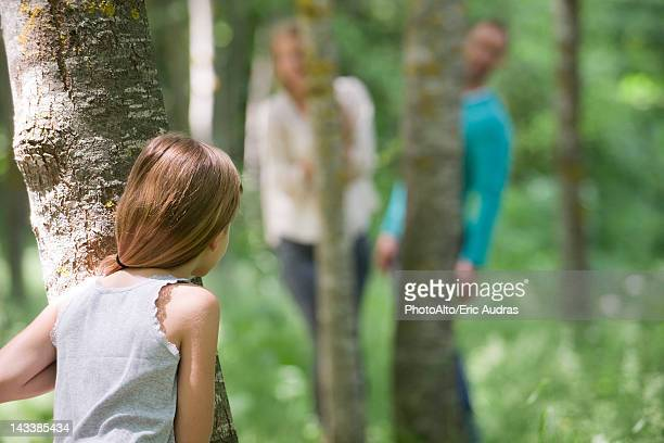 Girl playing hide and seek with parents in woods, rear view