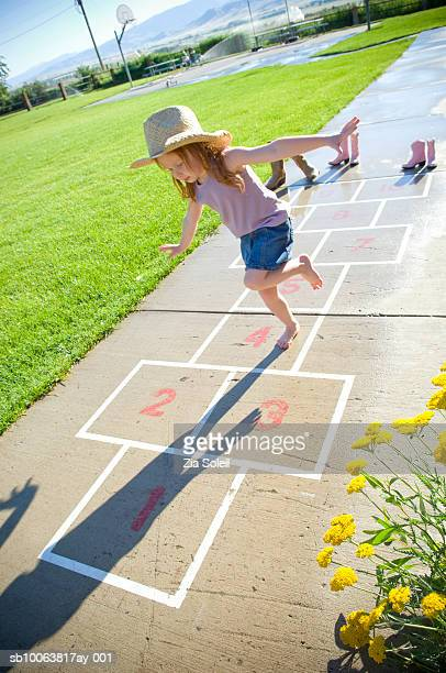 Girl (3-4) playing hopscotch in park