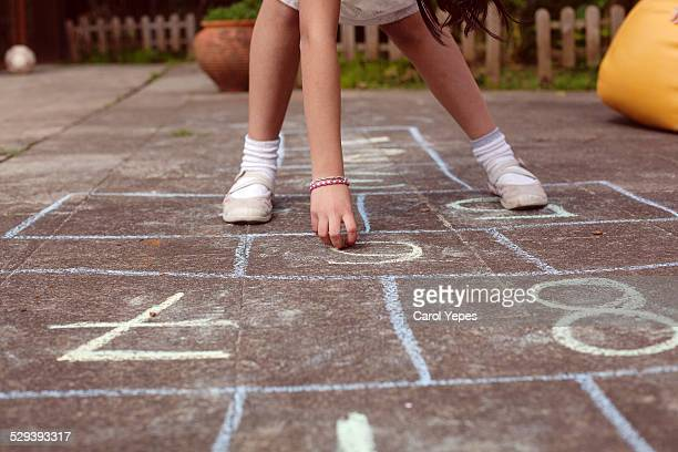 Girl playing hopscotch, low view
