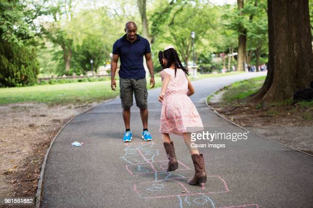 Girl playing hopscotch with father on road at park