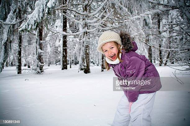 Girl playing in a winter forest