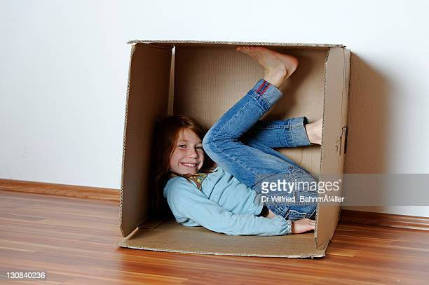 Girl playing in an empty cardboard box
