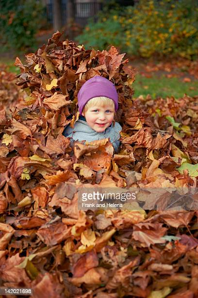 girl playing in autumn leaves - girl mound stock pictures, royalty-free photos & images