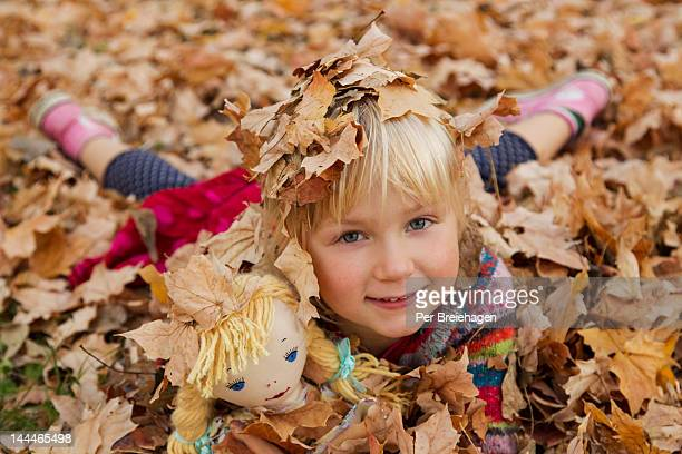 A girl playing in autumn leaves with her doll