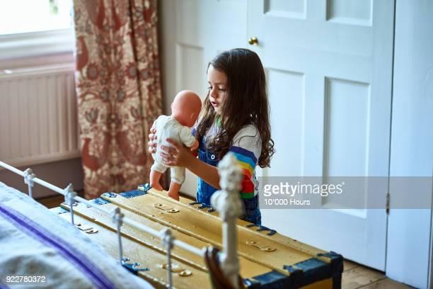 girl playing in bedroom - puppe stock-fotos und bilder