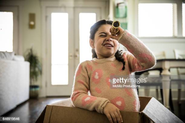 Girl (7yrs) playing in box with telescope