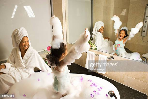 Girl playing in bubble bath as mother watches