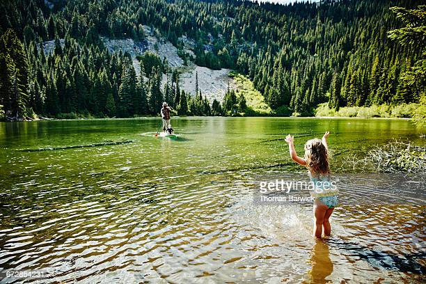 Girl playing in mountain lake waiting for father