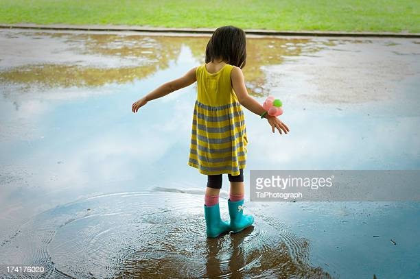 Girl playing in puddle with blue rain boots