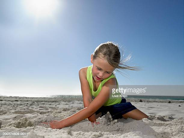 Girl (5-7) playing in sand on beach