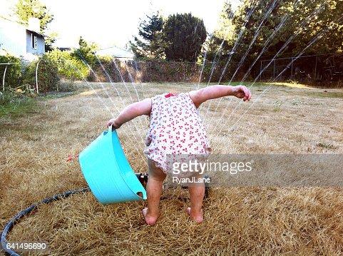 Girl Playing in Sprinkler