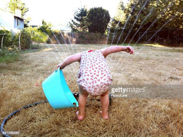 girl playing in sprinkler - refreshment stock pictures, royalty-free photos & images