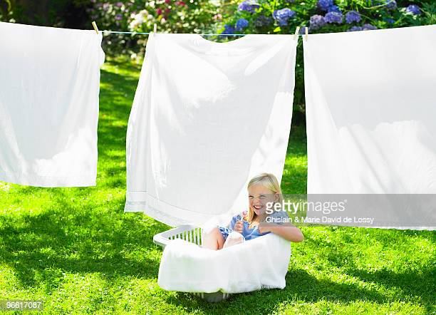 Girl playing in the laundry basket