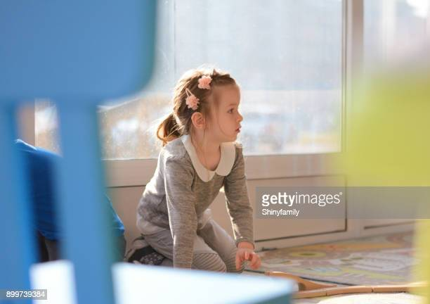 Girl playing in the playroom with education toys