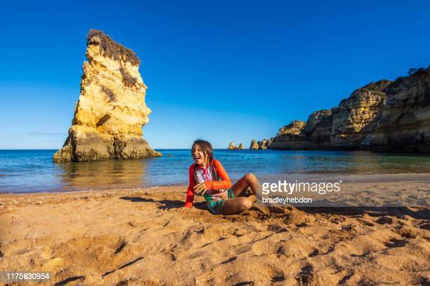 girl playing in the sand of praia dona ana beach in algarve, portugal - algarve stock pictures, royalty-free photos & images