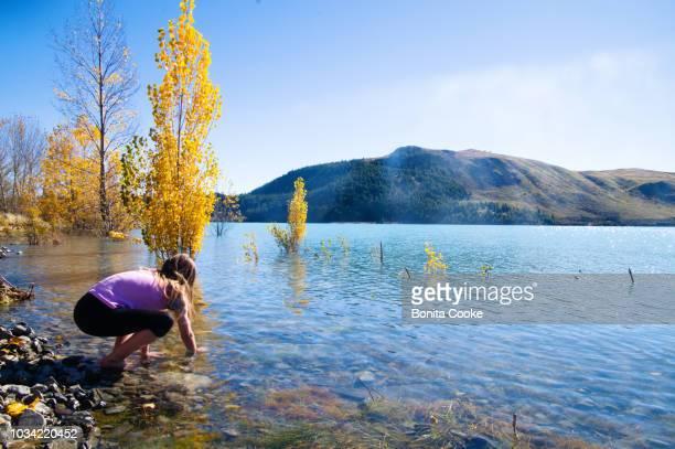 Girl playing in the water at Lake Tekapo, in Autumn