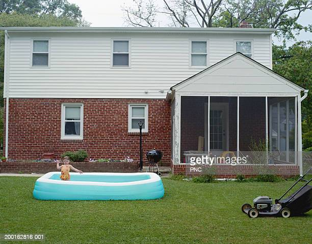 Girl (2-4) playing in wading pool, house in background