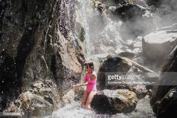 girl playing in waterfall, tofino, canada - vancouver island stockfoto's en -beelden