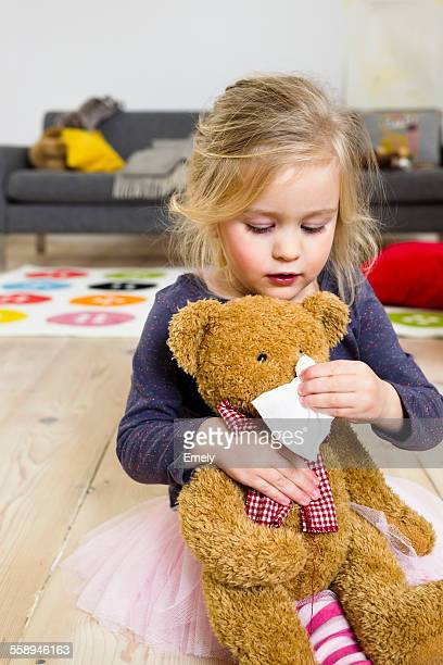 Girl playing mummy to bear