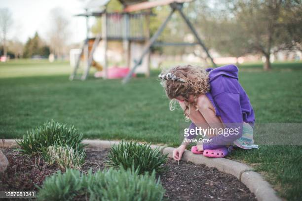 girl playing next to a garden - next to stock pictures, royalty-free photos & images