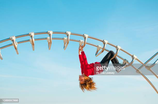 girl playing on a climbing frame - ジャングルジム ストックフォトと画像