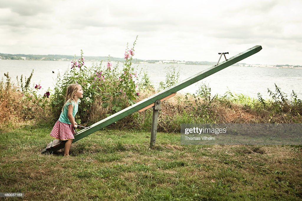 Girl playing on a seesaw : Stock Photo
