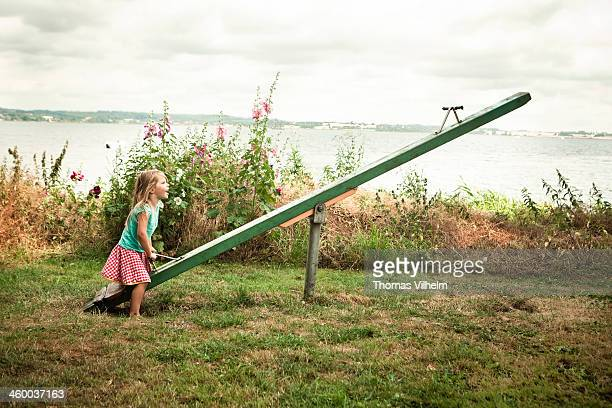 Girl playing on a seesaw