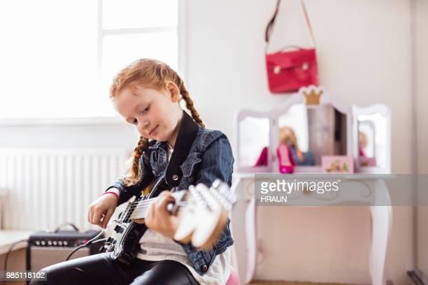 girl playing on an electric guitar - pizzicare le corde di uno strumento foto e immagini stock