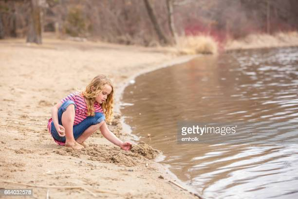 Girl Playing on Beach in Early Springtime
