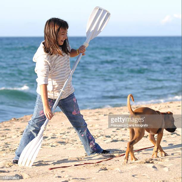 Girl playing on beach with oars of boat