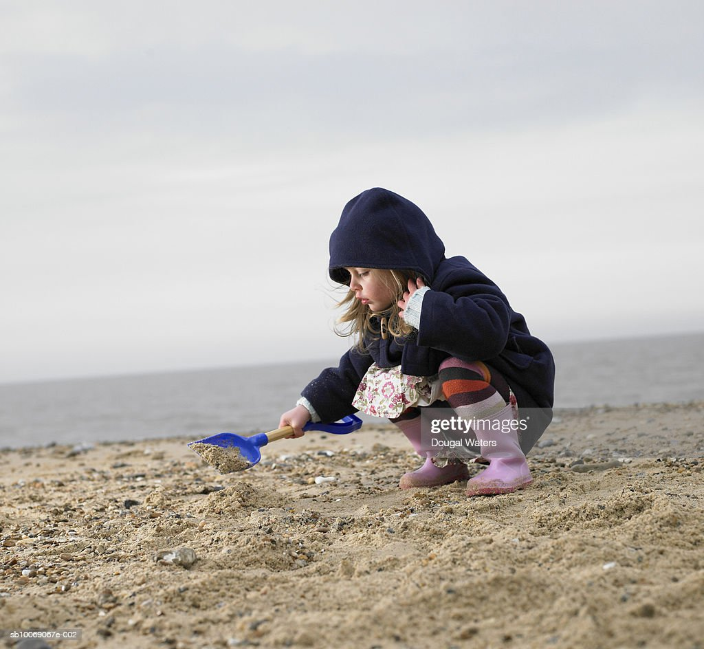 Girl (2-3) playing on beach with spade, side view : Stockfoto
