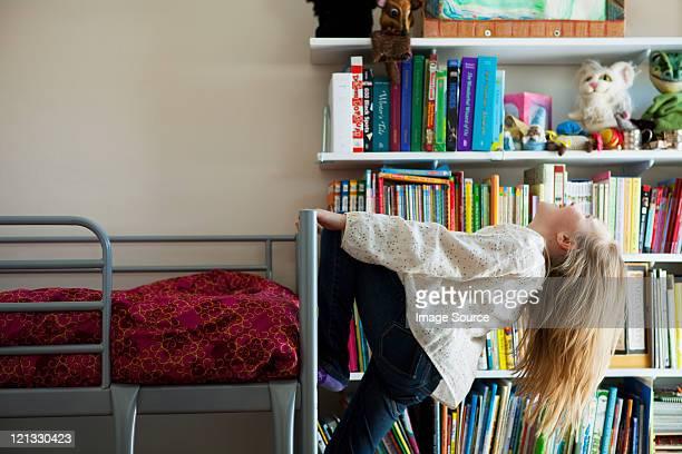 La jeune fille jouant sur lit superposé