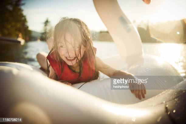 girl playing on inflatable swan in lake - heshphoto stock pictures, royalty-free photos & images