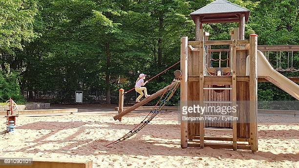 Girl Playing On Jungle Gym By Trees