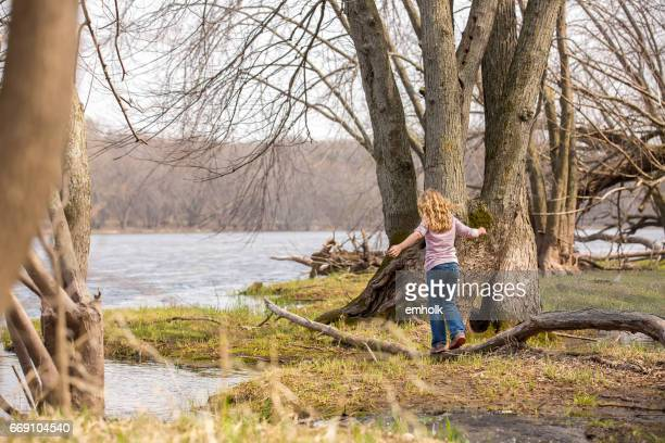 Girl Playing on Riverbank in Early Springtime