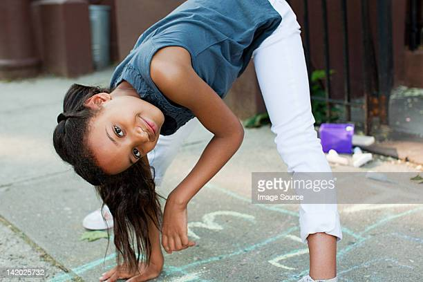 girl playing on sidewalk, smiling - little girls bent over stock photos and pictures