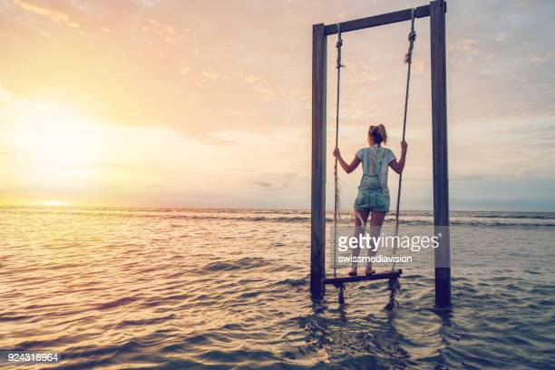girl playing on swing by the sea at sunset, indonesia - gili trawangan stock photos and pictures