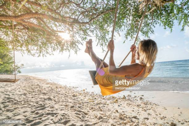 Girl playing on swing by the sea, Indonesia