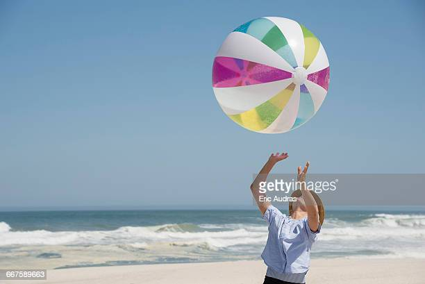 Girl playing on the beach with a ball