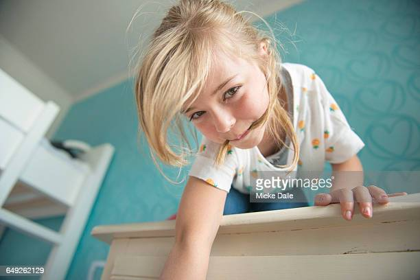 girl playing on top of the closet in bedroom - くわえる ストックフォトと画像