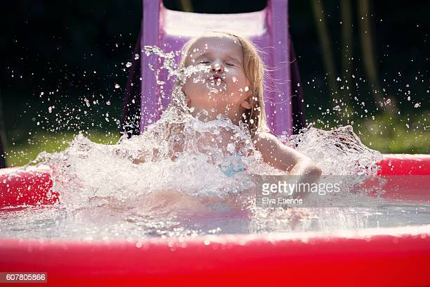 Girl (3-4) playing on water slide