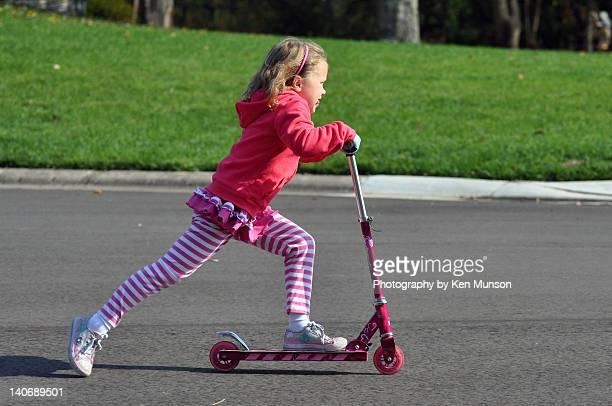 Girl playing outdoor with scooter