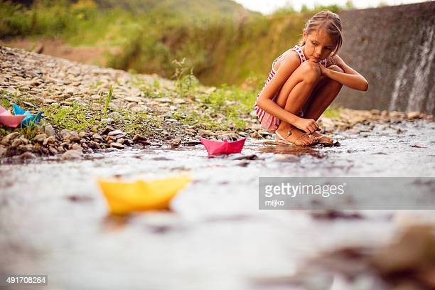 Girl playing paper boats on the river
