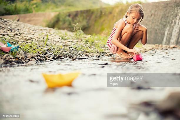 Mädchen spielt Papier-Boote auf dem Fluss