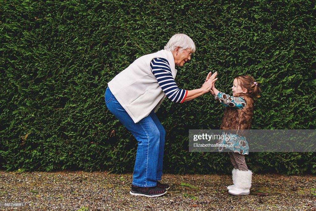 Girl playing pat-a-cake with her grandmother : Stock Photo