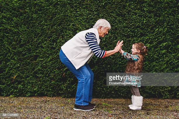 girl playing pat-a-cake with her grandmother - grandmother stock pictures, royalty-free photos & images