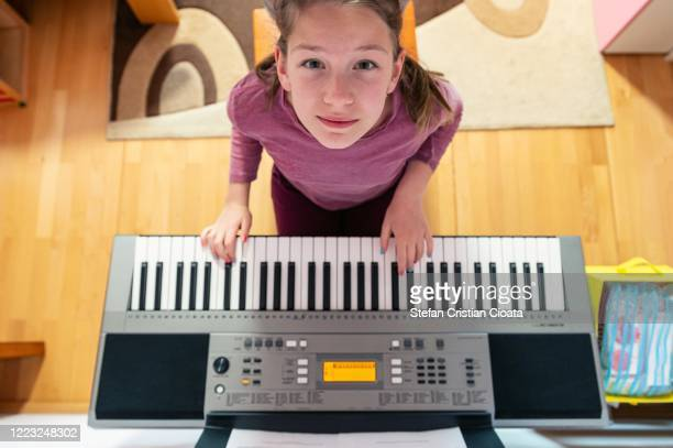 girl playing piano at home - keyboard player stock pictures, royalty-free photos & images