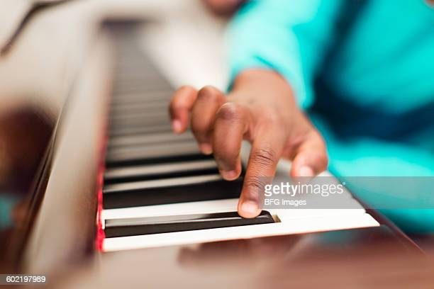 Girl (6-7) playing piano, Cape Town, South Africa