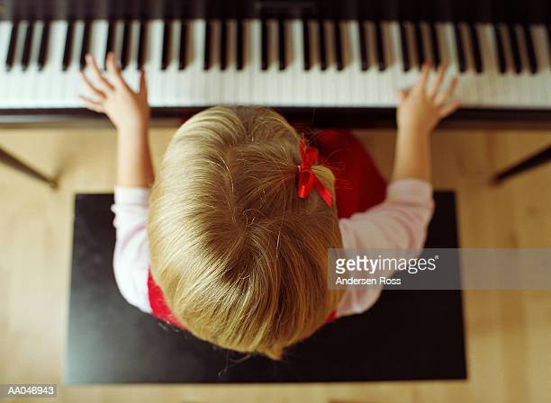 Girl (5-7) playing piano, close-up, overhead view