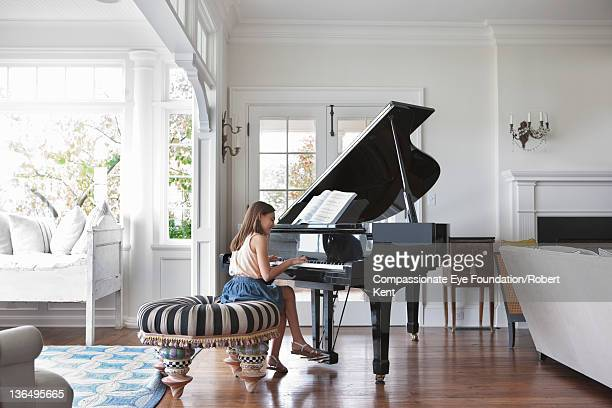 girl (10-11) playing piano in living room - grand piano stock photos and pictures